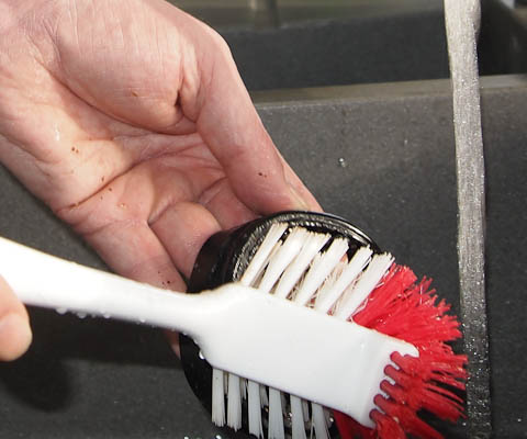Scrubbing the feed guard with a washing up brush